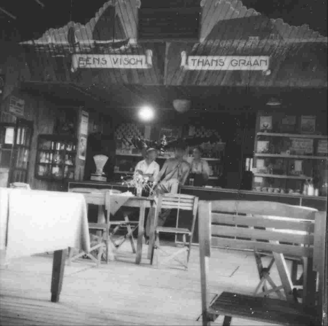 The canteen of work camp Nagele, managed by the Smit family. On the wall above the bar and shop the motto 'Eens visch thans graan' (Once fish, now wheat).1942-1948.