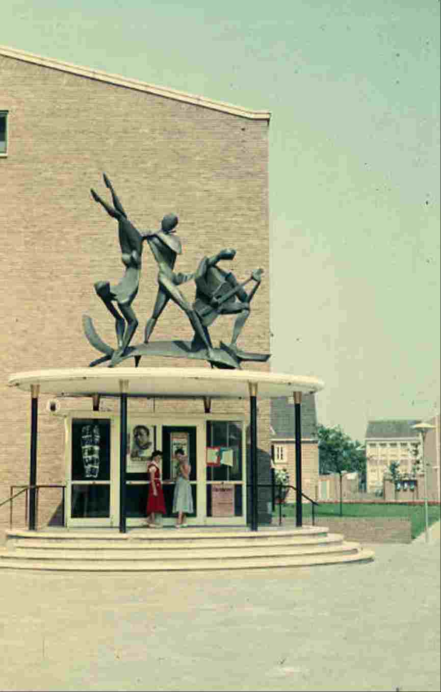 Theatre 't Voorhuys was completed in 1953, after a design of A.D. van Eck, as a multifunctional building including a theatre and exhibition hall. Here we see the entrance to the theatre in 1955 with the bronze sculpture The Three Muses by J. Bons.