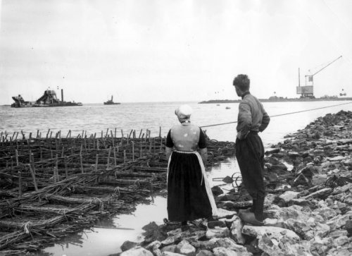 A man and a woman in Urk traditional costume are watching the construction of the dike from Lemmer to Urk, as a result of which Urk will stop being an island. Urk, 1936. The start of the construction of the Noordoostpolder.