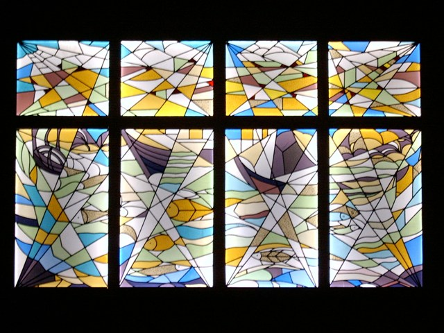 The stained glass window by artist Jan Meine Jansen was salvaged from demolition in 1995. The piece was renovated and hangs in the Exhibition hall of Theatre 't Voorhuys since 6 October 1995. The eight panels of the stained glass window represent the emerging Noordoostpolder: fishes, lands and shipwrecks.
